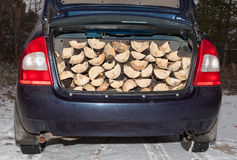 Car carries firewood in the trunk Stock Photo