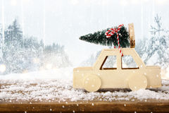 Car carrying a christmas tree in front of winter landscape Royalty Free Stock Photos