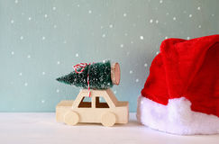 car carrying a christmas tree next santa claus hat Royalty Free Stock Photo