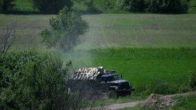 The car is carrying firewood near field.  stock footage