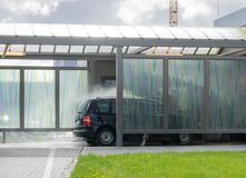 Car in a carwash center. Black car in a carwash center, building with green field in the foreground Royalty Free Stock Photo