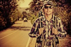 Car catcher. Young man tourist hitchhiking along a road Stock Images
