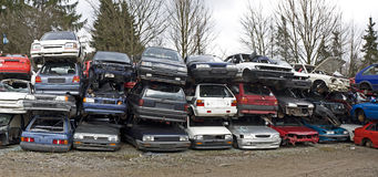 Wrecked cars. Stacked in an outdoor scrap yard royalty free stock photo