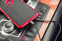 Car charger for the mobile phone. Phone charging in luxury car. Stock Photos