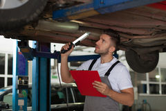 Car chassis inspection. Focused mechanic holding lamp and clipboard standing under the car and checking a chassis Royalty Free Stock Image