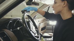 Car cleaning - attractive young woman is washing interior of a luxury vehicle with a brush. Close up Stock Images