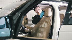 Car cleaning - attractive young woman is washing interiot of a luxury vehicle