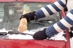 Car cleaning the snow from the car with a straw broom Royalty Free Stock Images