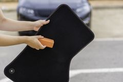 Car cleaning on the street. Someone cleaning a car mat Royalty Free Stock Photography