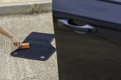 Car cleaning on the street. Someone cleaning a car mat Royalty Free Stock Photos