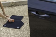 Car cleaning on the street. Someone cleaning a car mat Stock Photography