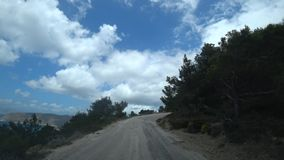 Car climbing to the mountains along a steep narrow road along the sea, view from the car.  POV shot