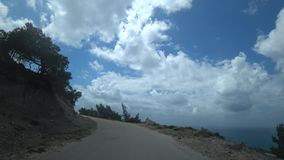 POV shot. Car climbing to the mountains along a steep narrow road along the sea, view from the car