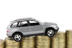 Car On Coins. A new car on a rising stack of coins, above which is an  white background Stock Photo