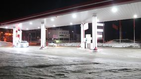 Car comes to petrol station and refuel at night in winter stock video