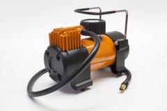 Car compressor on light background. Orange electric compressor for car on light background Royalty Free Stock Images