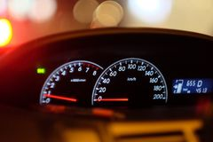 Car console Dashboard gages for a car  waiting in a traffic jam. At evening Royalty Free Stock Photo
