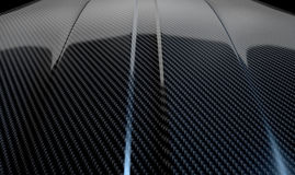 Car Contour Carbon Fibre. An abstract section of the contours of a carbon fibre automobile bonnet with dramatic lighting on a dark studio background Stock Image