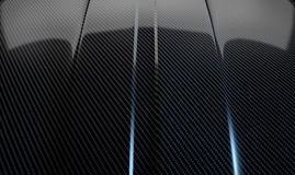 Car Contour Carbon Fibre. An abstract section of the contours of a carbon fibre automobile bonnet with dramatic lighting on a dark studio background royalty free stock images