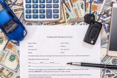 Car contract, toy car, dollar, calculator pen pencil. Stock Photo