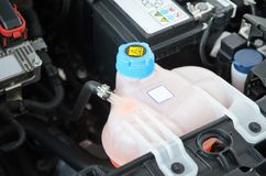 Car Coolant Reservoir. Close-up coolant reservoir under hood coolant engine car truck Stock Photos