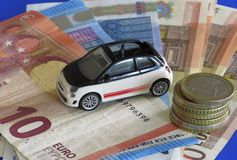 Car costs. Car, bank-notes and coins: buy, finance, rent or insurance car concept Royalty Free Stock Images