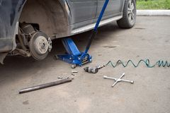 The car costs without a wheel on a jack during repair. Car repair. The car costs without a wheel on a jack during repair stock image
