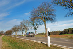 Car on a country road. The image shows a silvcar that is driving on a country road. On the right side of the street is a couple of trees that already have lost royalty free stock photo