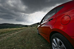 Car on country road. Red car driving on country road in moody day. Wide angle view Stock Photos