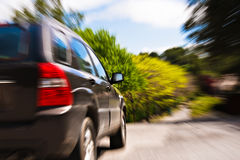 Car on countryside road. Read view of sport utility vehicle travelling on countryside road, zoom effect giving impression of speed Stock Photography