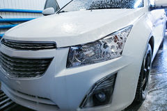 Car covered with foam in car wash. White modern car covered with foam in car wash Royalty Free Stock Images