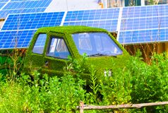 Car covered in grass. With solar panels in the background stock photo