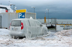 A car covered with ice layer. A photo of a car parked near to sea at winter. The wind has blown waves onto the car and created thick ice layer on the vehicle Stock Photo