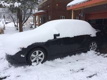 Car covered in snow. Black car covered in fresh snow royalty free stock images