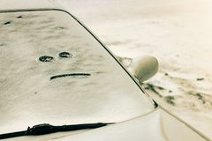 The car covered with snow with a evil face on the glass. Winter landscape stock photography