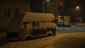 Car is covered with snow. Heavy snowfall in the city at night. stock video