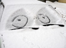 Car covered with snow with a painted on the windshield mug Stock Photos