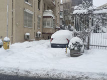 Car covered in snow on a parking lot of an apartment during wint Stock Images