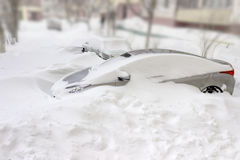 Car covered with snow among snowdrifts Stock Photos