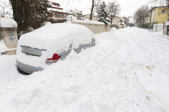 Car covered with snow in winter. Car covered in snow in front of suburban townhouses after a big winter snowstorm Royalty Free Stock Image