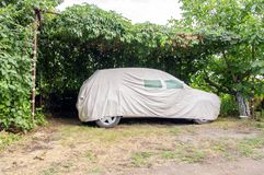 Car covered with a tarpaulin for cars royalty free stock photo