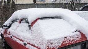 The car, covered with thick layer of snow. Negative consequence of heavy snowfalls. parked cars. Covered with snow during snowing in winter time stock photography
