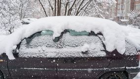 The car, covered with thick layer of snow. Negative consequence of heavy snowfalls. parked cars. Covered with snow during snowing in winter time stock images