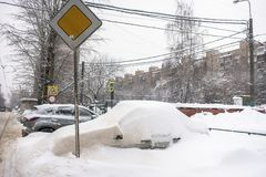 The car, covered with thick layer of snow, in the yard of residential house in provilcial town. Negative impact of heavy snowfall. Yards and surrounding stock image