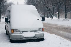 Car covered with white snow in the city. Minibus under the snow. Sleet slush, ice covering on the roads, and southeastern. Car covered with fresh white snow in royalty free stock image