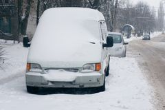 Car covered with white snow in the city. Minibus under the snow. Sleet slush, ice covering on the roads, and southeastern. Car covered with fresh white snow in stock photo
