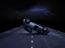 Car crash. Mini car crashed on highway during thunderstorm at night. There's a lightning over the black stormy sky and night city on the horizon Stock Image