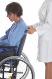 After the car-crash. Nurse is pushing her patient on a wheelchair Stock Photo