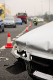 Car crash. A damaged vehicle rests at the side of the highway following a collision Royalty Free Stock Image