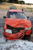 Car Crash. Red automobile with front end badly damaged after a collosion with another car Royalty Free Stock Image